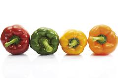 Red, green, yellow and orange capsicums Stock Photos