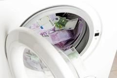 Euro banknotes in a washing machine, symbolic of money laundering Stock Photos