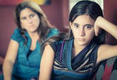 Defiant teenage girl and her worried mother Stock Photos