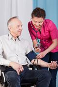 Nurse measuring blood pressure of disabled Stock Photos
