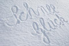the word schnee-glueck, snow happiness, written on an untouched blanket of sn - stock photo