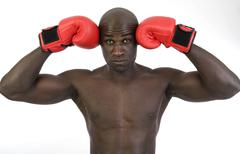 dark-skinned, athletic man, 30, wearing boxing gloves - stock photo