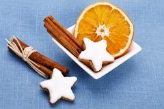 Cinnamon sticks with dried slice of orange and star-shaped cinnamon cookies i Stock Photos