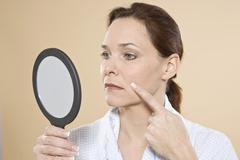 Woman checking her wrinkles with a hand mirror Stock Photos