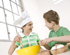 girl wearing a chef\'s hat and a boy preparing a dough together - stock photo