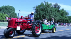 Rural small town parade features tractor and manure spreader Stock Footage