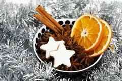 Star-shaped cinnamon cookies with dried slices of orange, cinnamon sticks and Stock Photos