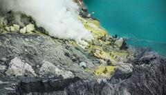 Sulfur miners at work inside crater of Ijen volcano Stock Photos