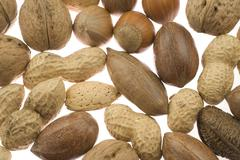 various nuts in their shells, brazil nuts, peanuts, hazlenuts, walnuts, pecan - stock photo