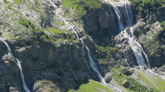 Waterfalls flowing down green mountain slope, beautiful scenery, click for HD Stock Footage
