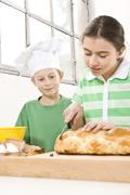 boy wearing a chef\'s hat watching a girl while she is cutting a braided yeas - stock photo