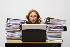 telephoning businesswoman, 41 years, with notebook and piles of documents - stock photo