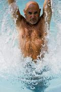 Active senior citizen jumping out of the water Stock Photos