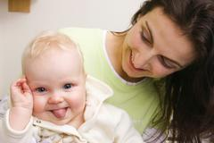 Stock Photo of mother, 32 years old, with smiling baby, 7 months old