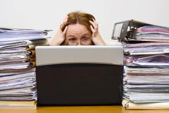 overworked businesswoman, 41 years, with notebook and piles of documents - stock photo