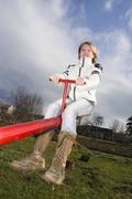 Girl, 11 years, on a seesaw Stock Photos