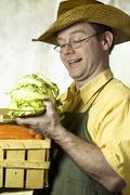 Greengrocer, portrait of a man with straw hat and basket full of vegetables Stock Photos
