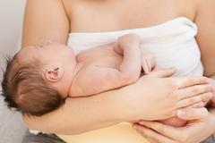 Mother holding newborn baby in her arms. Stock Photos