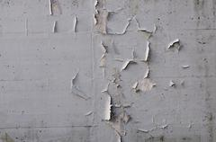 grey paint peeling off a concrete wall, humidity - stock photo