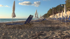 End of vacation day on Lefkada beach with sunbeds and closed umbrellas in sunset Stock Footage