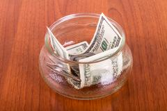Stock Photo of dollar banknotes in glass bowl