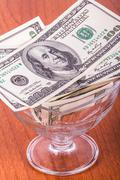 dollar banknotes in glass bowl - stock photo