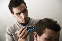 Young man of mediterranean origin cutting a friend's hair, germany, europe Stock Photos