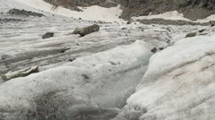 Dirty melting snow, water stream running down the hill, spring, click for HD Stock Footage