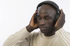 dark-skinned man, 30, wearing headphones - stock photo