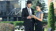Business couple standing together and work on the tablet - stock footage