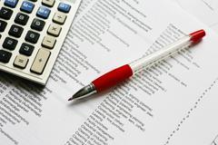 Calculator and red pen on a technical description Stock Photos