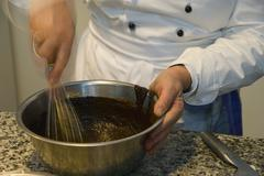 cooking course, creation of a light-dark chocolate tarte, hands whipping the  - stock photo