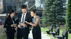 Company of three business people discussing a business deal on outside the offic - stock footage