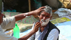 An old man being shaved at the barbershop in indian town. Stock Footage