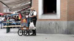 Senior man playing a street organ in the old town Stock Footage