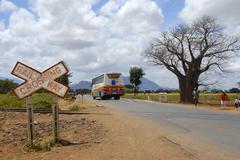 sign railway crossing with long distance bus on country road and baobab (adan - stock photo