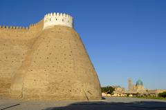 Side tower and wall of the ark fortress with minaret kalon in the background  Stock Photos