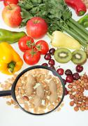 fruits, vegetables and nuts under magnifier - stock photo