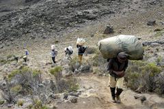 Local porters carry heavy loads kikelewa route kilimanjaro tanzania Stock Photos