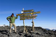 Successful mountaineer at the sign on the summit uhuru peak (5895 m) crater r Stock Photos