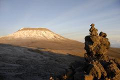 Fresh snow on kilimanjaro behind a rock formation kikelewa route tanzania Stock Photos
