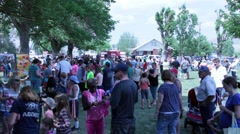 Crowds mingle in small town city park to celebrate annual summer festival Stock Footage