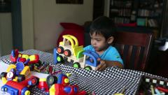 Cute Asian Boy Plays With His Toys At The Table Stock Footage