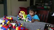 Stock Video Footage of Cute Asian Boy Plays With His Toys At The Table
