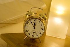 Alarm clock on bed table Stock Photos