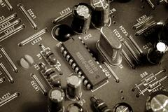 Close up of a microchips and various electronic components on a circuit board Stock Photos