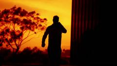 Sunset Silhouette 05 Man walking towards camera with cell phone in hand Stock Footage