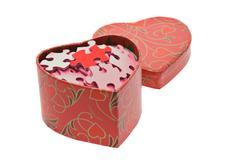 red and pink jigsaw puzzles in heart shape gift box - stock photo