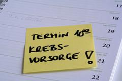 """Yellow reminder note """"termin"""" (cancer checkup appointment) on the page of a c Stock Photos"""