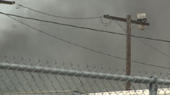Smoke blowing with a telephone/powerline pole and a fence in the foreground Stock Footage